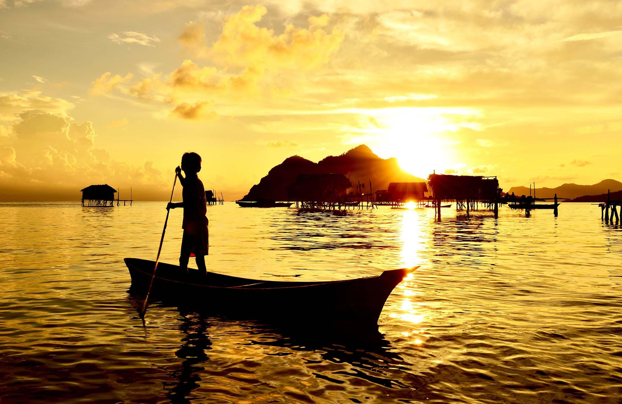 borneo-sabah-semporna-maiga-island-kid-paddling-on-a-boat-near-bajau-laut-village-cover
